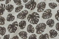 Deko-stof i hørlook med jordfarvede filodendron blade.