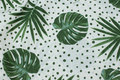 Hvid deko-stof med grønne blade og prikker.