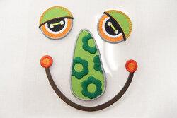 Fjollet ansigt strygemærke grønt