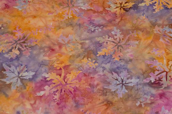 Batik-bomuld i orange og lyslilla med spredte blade