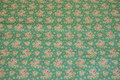 Jadegrøn bomuld med små rosa blomster.