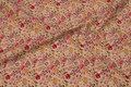 Cremefarvet bomuld med røde, lilla og gule blomster.