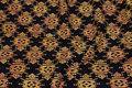 Sort batik-bomuld med gyldent mønster.