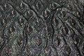 Pailletstof med påfuglemønster i sart grønlige farver