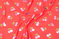 Coral red cotton-jersey with shiny, pink cherries.