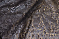 Flot netstof, i mørk brungrå, med påsyede pailletter.