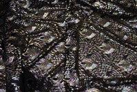 Flot pailletstof med påfuglemønster på sort bund af mesh