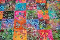 Batik-patchwork syet i 10 cm firkanter i røde, orange, pink og blå nuancer