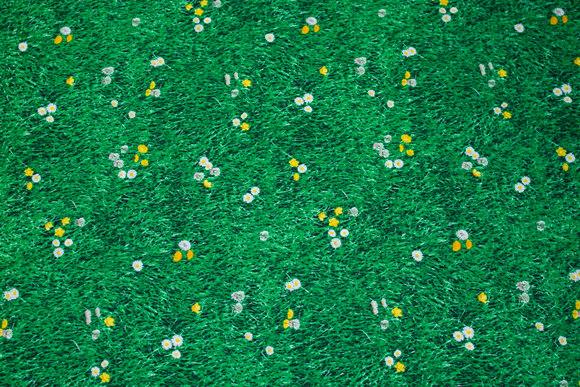 Grøn patchwork-bomuld med græs, små tusindfryd og mælkebøtter
