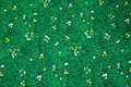 Grøn patchwork-bomuld med græs, små tusindfryd og mælkebøtter.