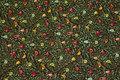 Skovgrøn patchwork-bomuld med små frugter og fuglehuse.