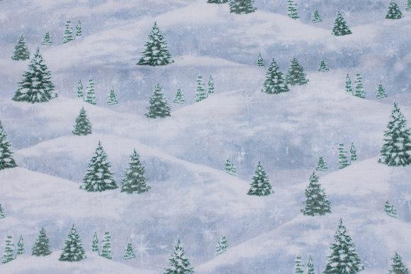 Blåhvid patchwork-bomuld med grantræer i sneen