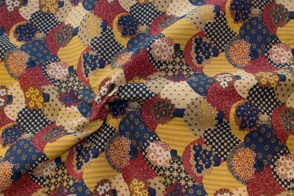 Dæmpede gul-røde-blå farver på patchworkbomuld