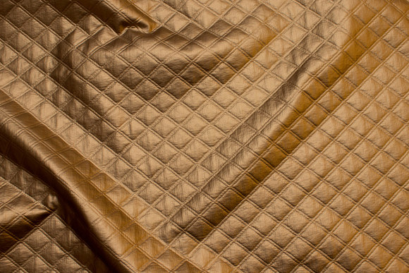 Præget quilt i guldkobber-farvet