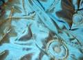 Flot, broderet quiltet taft med guldbroderi på turkis.