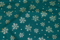 Dark green christmas-cotton with ca. 3-5 cm gold snow-crystals.