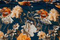 Petrolfarvet viscosejersey med flotte blomster i rustorange og råhvid