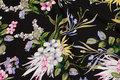 Sort viscose mousselin med store, flotte hvide, røde og blå blomster.